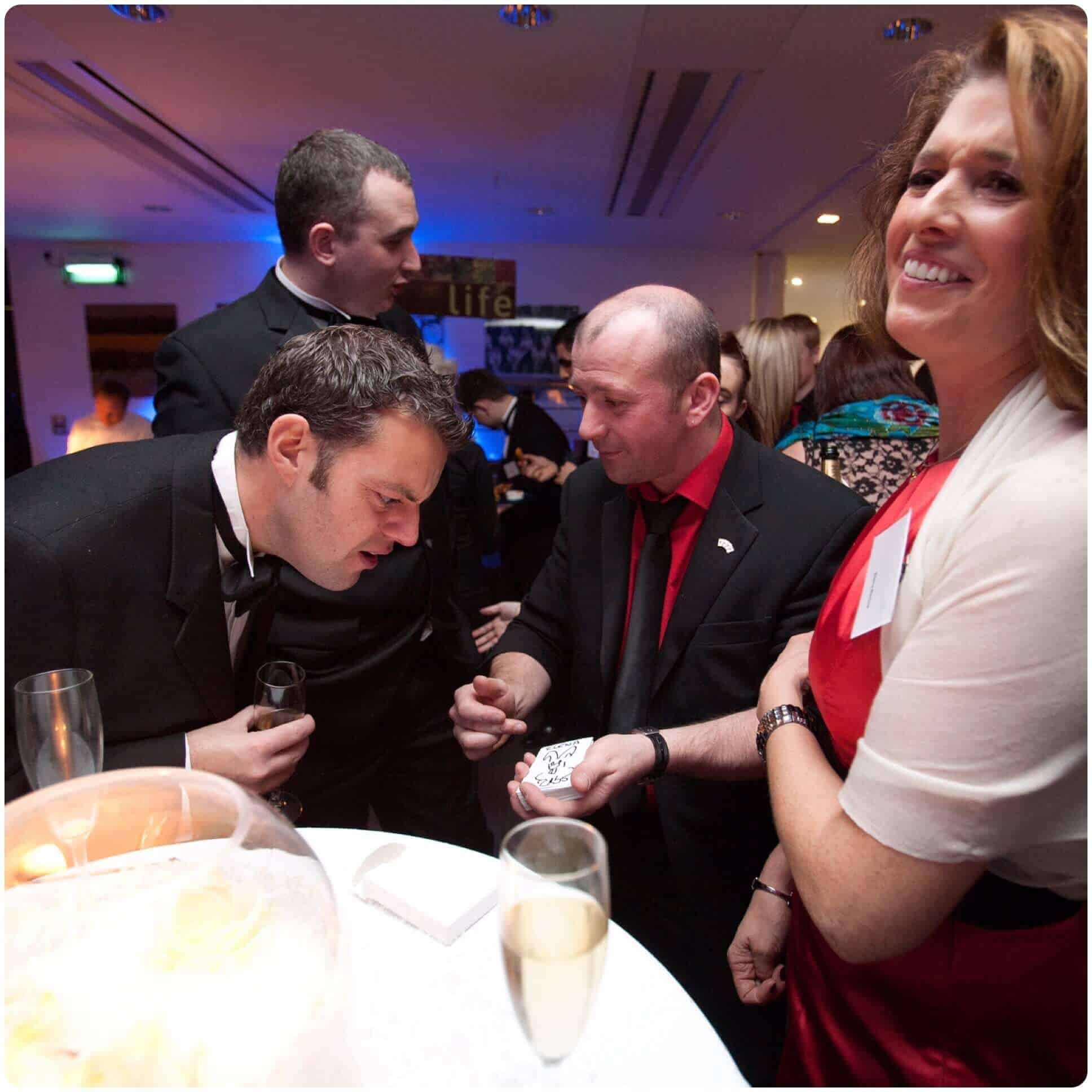 Guests being baffled by the corporate magic of Will Gray at a back tie dinner