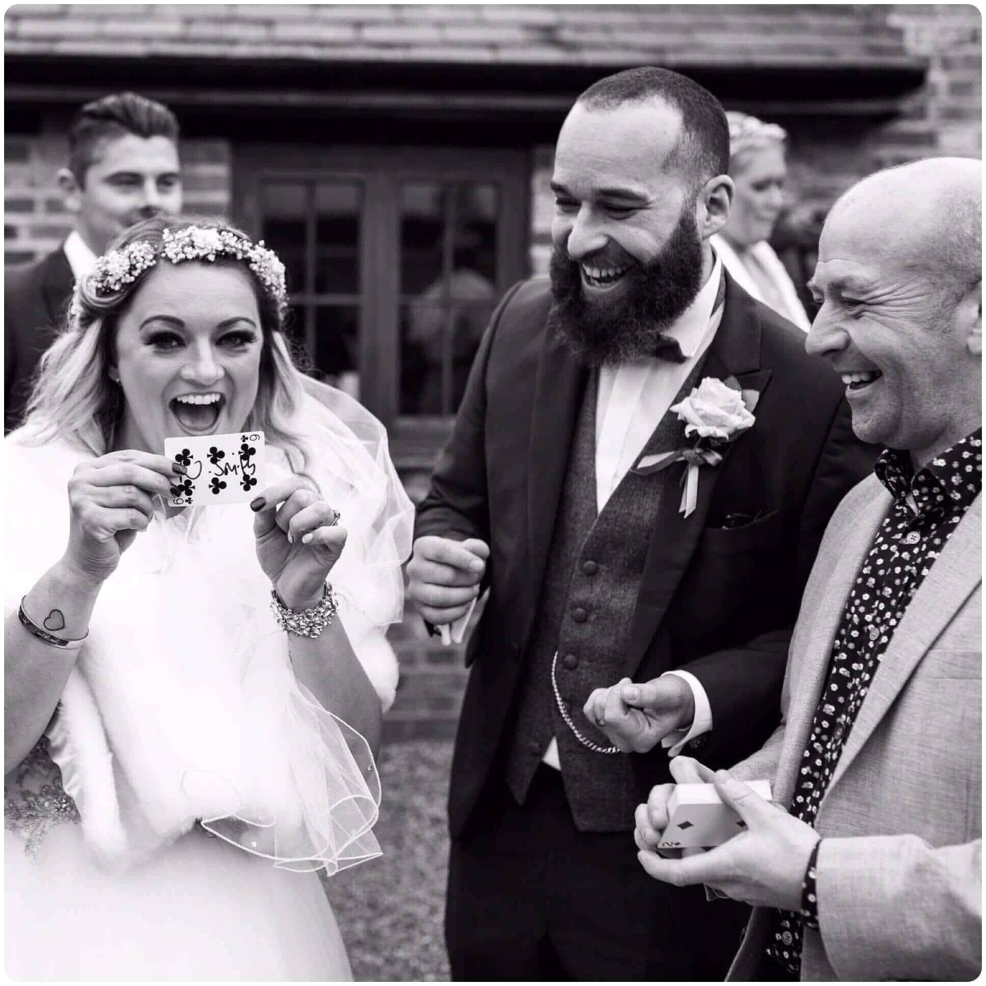Birmingham magician Will Gray performing a card trick to an amazed bride and groom